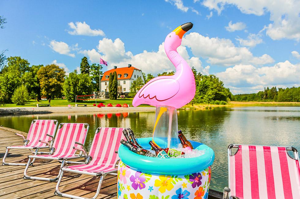 Solstolar på bryggan och ishink flamingo med herrgården i bakgrunden